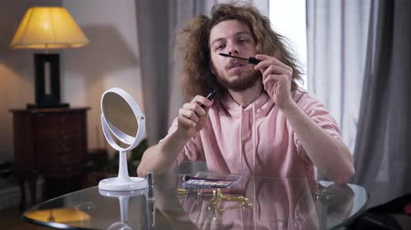 щеткой : Middle shot of young Caucasian man opening mascara and looking at brush. Male intersex person choosing makeup cosmetics indoors. Self perception, gender identity.