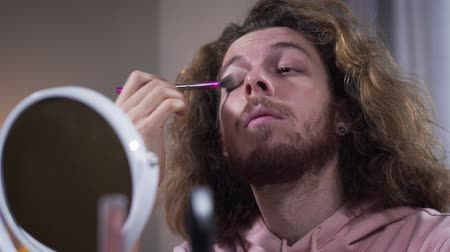 humanidade : Portrait of positive intersex Caucasian person doing makeup, looking at mirror and smiling. Binary gender man with long curly hair applying eye shadows. Gender identification, minority, lifestyle.