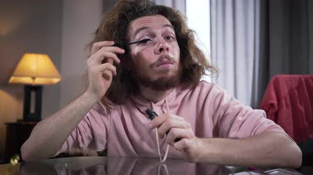 kosmetyki : Portrait of bearded Caucasian man with brown eyes and long curly hair looking at camera and applying mascara. Intersex guy doing makeup on one side of face. Transgender people, gender identity.