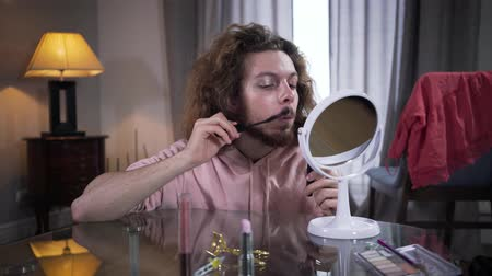 bigodes : Front view of young Caucasian man looking at mirror and applying mascara on mustaches. Intersex person doing makeup on one side of face. Gender identity, man and woman in one body.
