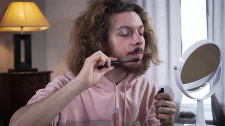 two gender : Adult Caucasian intersex person looking at mirror and applying mascara on beard. Man perceiving himself as a woman. Gender identity, binary gender.