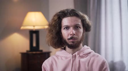 sexualita : Face of young Caucasian man with long curly hair turning head and showing part with applied makeup. Self identification of intersex people. Dostupné videozáznamy