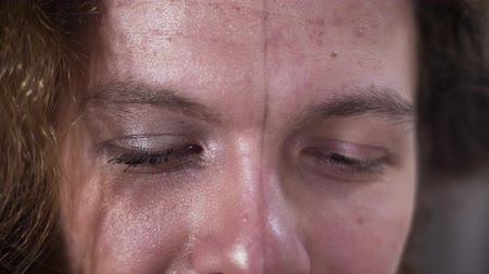 haklar : Close-up of mans brown eyes. Face divided into two parts, feminine and masculine. Binary gender, self identification, intersex people. Stok Video
