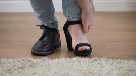 cipő : Close-up of Caucasian adult man putting on mens broggi boot and womens high heel shoe. Illustration of binary gender, intersex people.