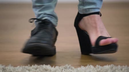 cipő : Adult Caucasian intersex person standing in one mens broggi boot and one womens high heel shoe. Extreme close-up of male feet turning to left and right. Gender identity, self identification. Stock mozgókép