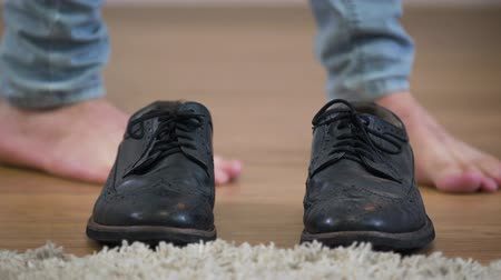 pisos : Close-up of black broggi shoes standing on the floor, male Caucasian feet coming up. Young man putting on boots and leaving the shot. Fashion, style.