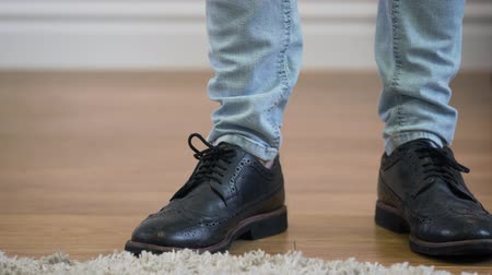 stomping : Male Caucasian feet in jeans and broggi shoes coming into shot, stopping, and leaving. Man in elegant boots. Lifestyle, fashion.