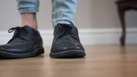 zatáčka : Unrecognizable male Caucasian person standing with legs crossed, stepping aside, turning and leaving. Close-up of mens elegant footwear. Fashion, shoes, boots. Dostupné videozáznamy