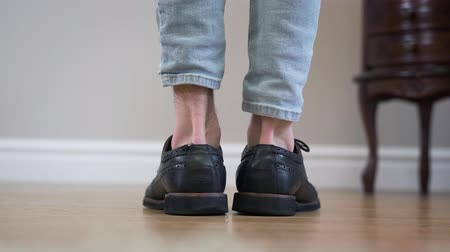 cipő : Close-up of black broggi boots turned to both sides. Unrecognizable Caucasian adult man turning feet and leaving. Footwear, accessories, fashion. Stock mozgókép