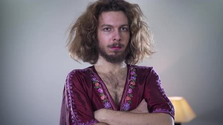 self perception : Portrait of adult Caucasian man in womens dress with makeup on face looking at camera. Intersex person expressing his feminine identity. Camera moving around person from right to left.