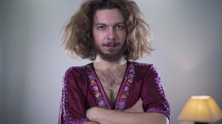 self perception : Camera moving from left to right around young bearded Caucasian man with long curly hair and brown eyes looking at camera and smiling. Portrait of positive intersex person standing with hands crossed.