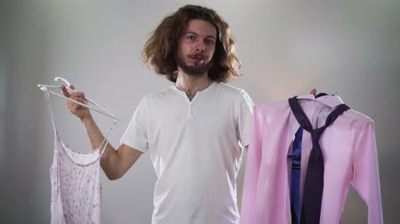 seçme : Focused adult Caucasian man with makeup on one side of face holding two hangers deciding on outfit. Intersex person choosing womens dress, looking at camera and smiling. Self identity, transgender.