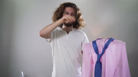 self perception : Portrait of young Caucasian intersex person choosing outfit between womens dress and male shirt. Handsome man erasing makeup, looking at camera and showing thumb up. Self identity, binary gender.