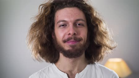 self perception : Close-up portrait of smiling Caucasian intersex man with makeup on one side of face looking at camera and screaming suddenly. Minority problems, discrimination, gender identity.