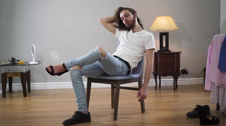 self perception : Middle shot portrait of young handsome Caucasian man sitting on chair touching hair and looking at camera. Intersex person wearing one male broggi boot and one female high heel shoe.