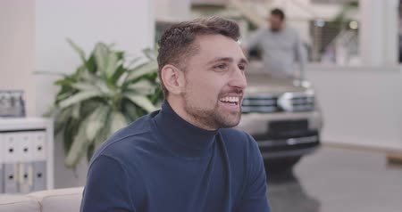 seçme : Close-up face of handsome Caucasian man sitting in car dealership and smiling. Young successful businessman resting after choosing new automobile. Car business. Cinema 4k footage ProRes HQ.