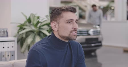 vista lateral : Side view of thoughtful Caucasian man sitting in car dealership and looking away. Successful handsome businessman resting after purchasing of new automobile. Car business. Cinema 4k footage ProRes HQ.