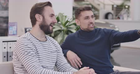seçme : Side view of two Caucasian handsome men sitting in car dealership, smiling, and talking. Young businessmen discussing car purchase in showroom. Car business. Cinema 4k footage ProRes HQ.