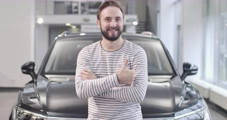 seçme : Portrait of smiling Caucasian man in stripped sweater showing thumb up in front of new car. Satisfied buyer posing with new automobile. Car dealership, car business. Cinema 4k footage ProRes HQ. Stok Video