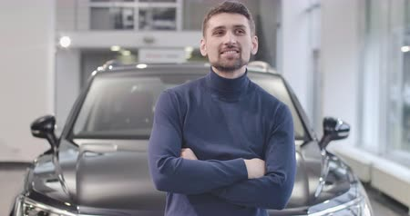 seçme : Close-up portrait of satisfied Caucasian man standing in front of new black car. Happy client with the purchased vehicle. Car dealership, car business. Cinema 4k footage ProRes HQ. Stok Video