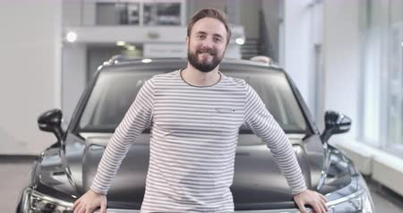 seçme : Happy bearded Caucasian guy in stripped sweater posing with new black car. Successful man buying vehicle in car delaership. Car business. Cinema 4k footage ProRes HQ. Stok Video