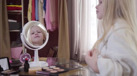vista lateral : Pretty Caucasian little girl admiring her reflection in mirror. Portrait of cute child with long blond hair in white bathrobe. Beauty, childhood, happiness. Focused on reflection.
