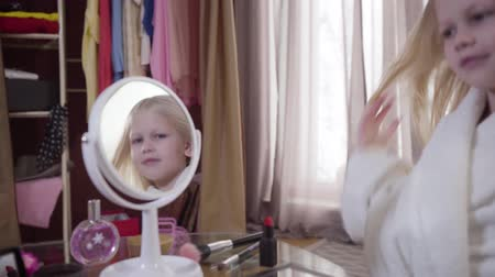 vista lateral : Blurred blond Caucasian girl in white bathrobe standing on the right and smiling. Focused on reflection of pretty child in round mirror. Happiness, style, leisure.