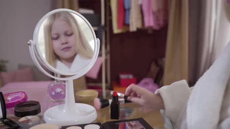 щеткой : Reflection in mirror of little cute Caucasian blond girl taking makeup brush for applying eye shadows. Stylish young lady spending free time at home. Lifestyle, fashion. Focused on cosmetics.