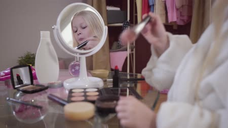 щеткой : Little blond Caucasian girl applying face powder. Pretty child in white bathrobe standing in front of table with cosmetics and reflecting in mirror. Fashion, lifestyle, beauty.