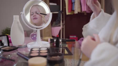щеткой : Little cute Caucasian girl holding makeup brush and applying eye shadows. Young blond lady doing makeup at home. Lifestyle, fashion. Focused on reflection in mirror.
