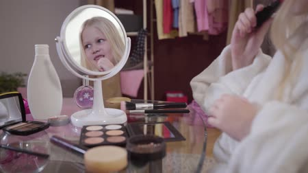kosmetyki : Happy little Caucasian girl applying red lipstick in front of mirror. Charming blond child using cosmetics indoors and smiling. Face of pretty kid reflecting in mirror.