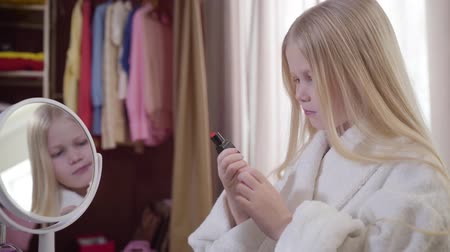 kosmetyki : Camera approaching to face of excited blond Caucasian child taking red lipstick from the table. Charming girl choosing cosmetics indoors. Fashion, style, beauty.