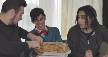 trzy : Three Caucasian male adult students sitting on couch and eating pizza. Boys talking and laughing indoors. Men having fun. Cinema 4k ProRes HQ.