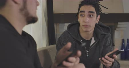 dialog : Close-up portrait of young Caucasian man with brown eyes and dreadlocks talking with male friend. Two confident guys discussing something indoors. Cinema 4k ProRes HQ.
