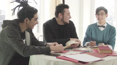 dialog : Three young Caucasian men sitting at the table, talking and laughing. Male university students studying together indoors. Friends enjoying studies. Education concept.