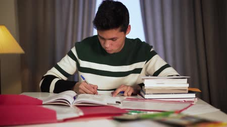 science : Portrait of concentrated Asian boy studying at the table. Handsome young college student writing in workbook indoors. Learning, lifestyle, education concept.