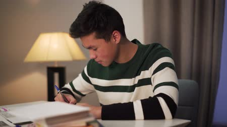 deha : Side view of excited Asian student doing homework indoors. Teenage boy sitting at the table with books and smiling. Education, intelligence, lifestyle.