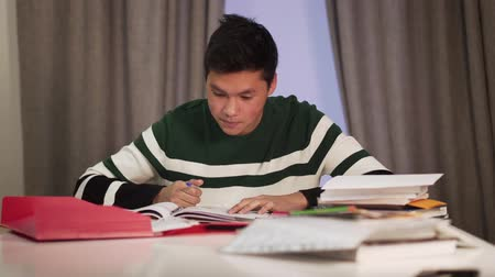 studente : Portrait of smart Asian male student doing homework at the table. Excited teenager making victory gesture and smiling. Education, intelligence, lifestyle, joy.