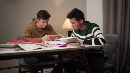 studente : Two college students sitting at the table with books and workbooks. Asian boy studying as his Caucasian friend using smartphone. Education, homework, lifestyle. Filmati Stock