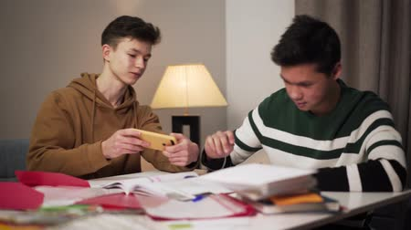 deha : Teenage Caucasian boy distracting his Asian groupmate from studies. Two male college students sitting at the table with books and talking. Boy with smartphone annoying concentrated teenager. Stok Video