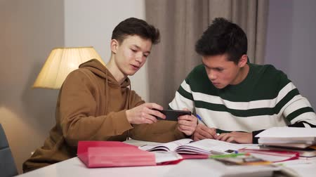 adolescente : Portrait of focused Asian boy doing lessons as his Caucasian groupmate annoying him. Teenager showing something to groupmate on smartphone. College life, college students, lifestyle.