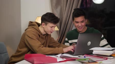 eleves : Clever Caucasian boy helping his Asian friend to deal with laptop. Friendly multiracial groupmates studying indoors in the evening. Education, intelligence, lifestyle.