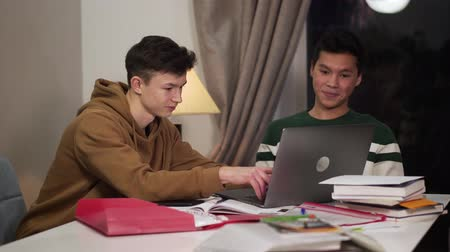 adolescente : Two intelligent smiling college students sitting at the table and using laptop. Happy Caucasian and Asian teenagers studying online and giving high five. Happiness, intelligence, education.