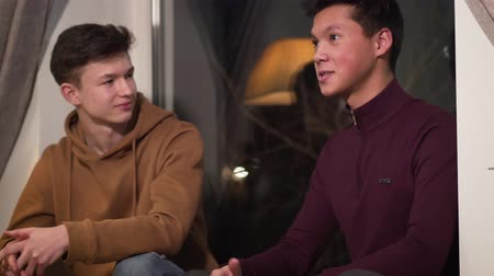 vriendschap : Portrait of Caucasian and Asian friends talking and giving dap. Teenage friends spending evening indoors. Happy people smiling. Friendship, support, lifestyle. Stockvideo
