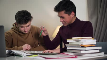 deha : Close-up portrait of two excited boys looking at map and discussing geography. Smiling Caucasian and Asian college students talking and giving dap. Lifestyle, joy, education concept. Stok Video
