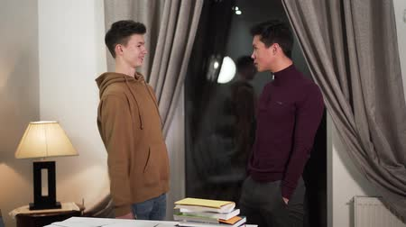 adolescente : Two multiracial boys arguing in the evening indoors. Asian and Caucasian college students standing in room and yelling at each other. Male friendship, relationship problems.