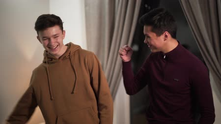 vriendschap : Portrait of Asian and Caucasian fellows looking at camera and smiling. Two teenage students standing indoors in the evening. Friendship, male friendship, lifestyle. Stockvideo