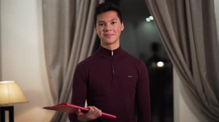 позирует : Portrait of confident Asian boy standing with documents folder, looking at camera and smiling. Happy college student posing indoors. Intelligence, education concept. Стоковые видеозаписи