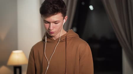 adolescente : Portrait of happy Caucasian teenager listening to music in headphones, looking at camera and smiling. Handsome young boy with brown eyes posing indoors in the evening. Lifestyle, hobby, happiness.
