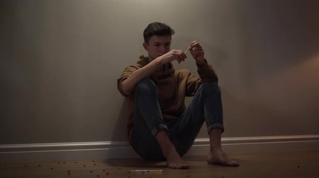 bağımlı : Portrait of addicted Caucasian boy sitting on the floor with syringe. Teenage boy in casual clothing having drug addiction. Drugs, adolescence, lifestyle.